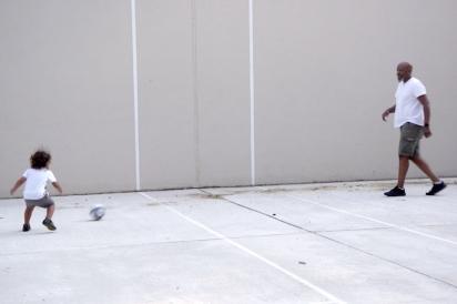 Mychal Johnson plays soccer with his son on a handball court