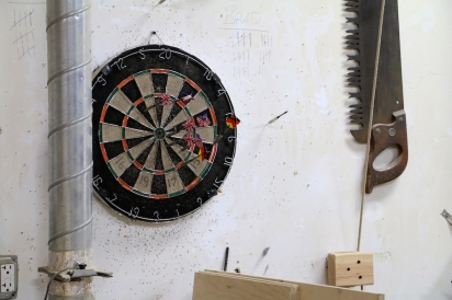 Friendly ongoing game of darts in the Bronx Wood Works workshop