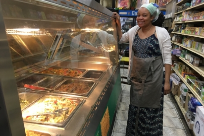 Co-owner Najan Compton stands near the hot food buffet, all items are vegetarian or vegan.