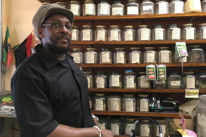 Co-owner of H.I.M Ital Oba Kenjah stands in front of a wall of herbs and spices