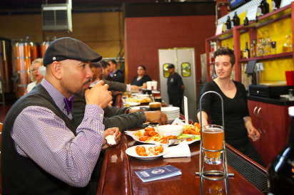 Ruben Diaz Jr enjoying wings and beer with Edible Bronx at the Chelsea Craft Brewing Company ribbon cutting