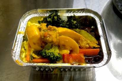 A small to-go box of barbequed soy chunks with pineapple, curried squash and carrots, mixed veggie noodles, and sautéed greens