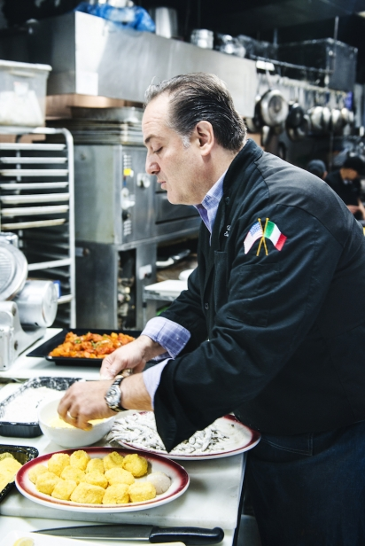 David Greco, owner of MIkes Deli in Arthur Avenue coating fish for frying