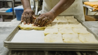 Baker at Kingston Tropical Bakery making Coco Bread by hand